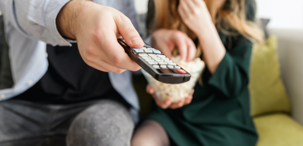 two people sitting eating popcorn whilst holding a TV remote. The image is to aid an article on how to find mac address for Amazon Fire TV Stick and other devices