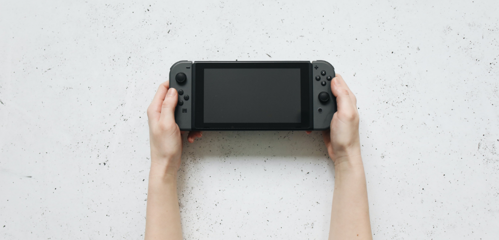 A pair of hands holding a Nintendo Switch, to highlight that here is where you can find how to find a mac address for your Nintendo console