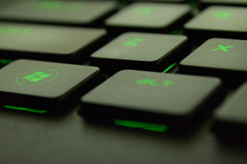 Black Keyboard with green blacklighting showing Windows key
