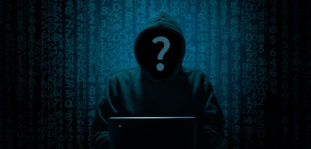 A hooded figure using a laptop. Do you have legally compliant guest WiFi?